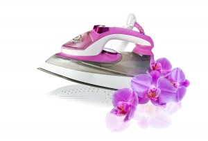 modern new pink electric iron and orchid flowers on white background